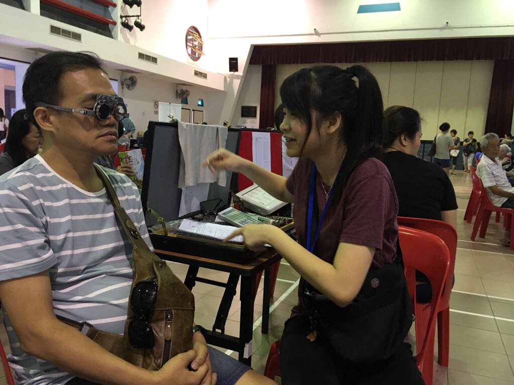 Volunteer optometrist Goh Jiahying checking a resident's glasses prescription during an eye screening conducted at Choa Chu Kang Community Centre on 8 October 2017.