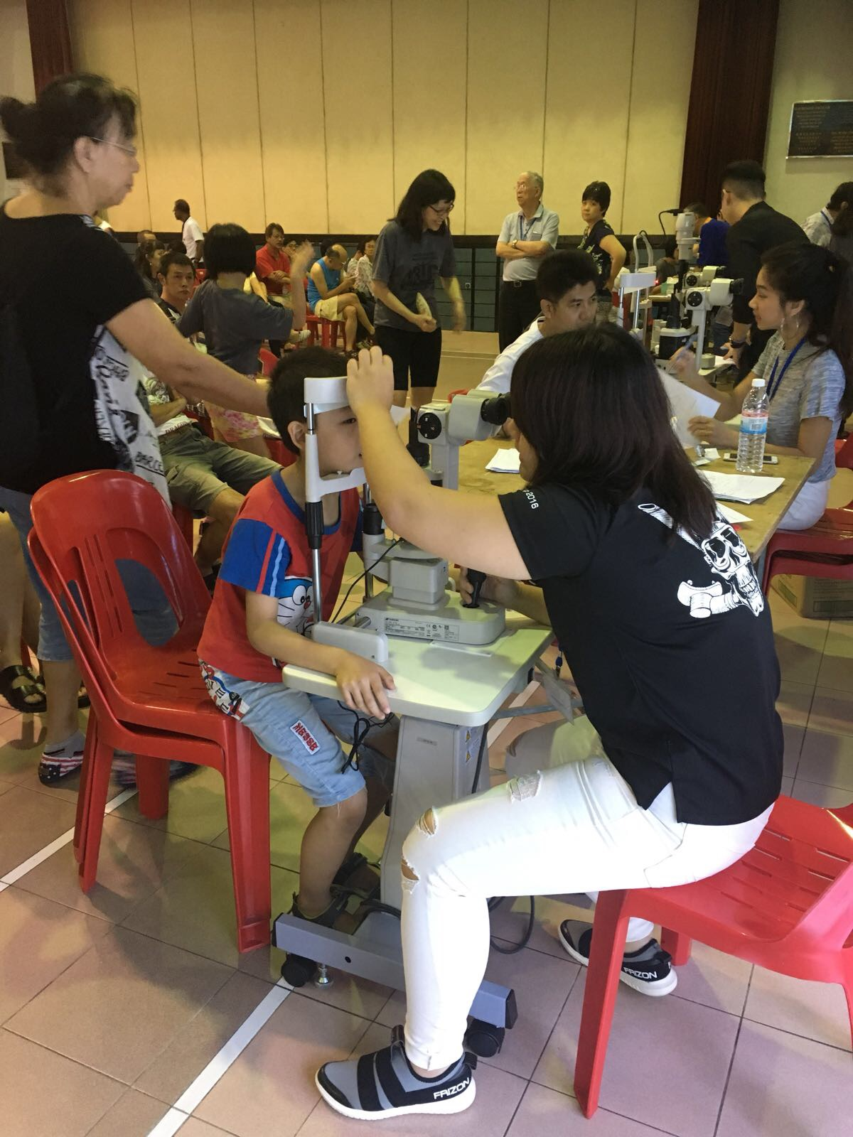 Volunteer optometrists examining the anterior segment of residents' eyes during an eye screening conducted at Choa Chu Kang Community Centre on 8 October 2017.